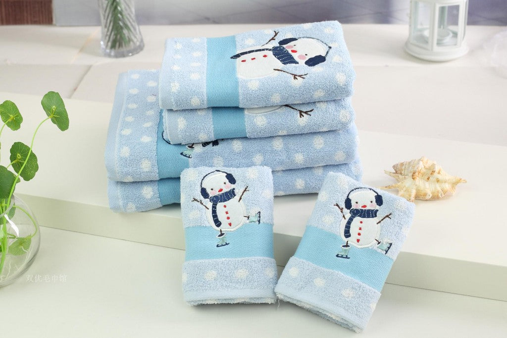 Light blue bathroom towels with an ice skating snowman design and white falling snow dots