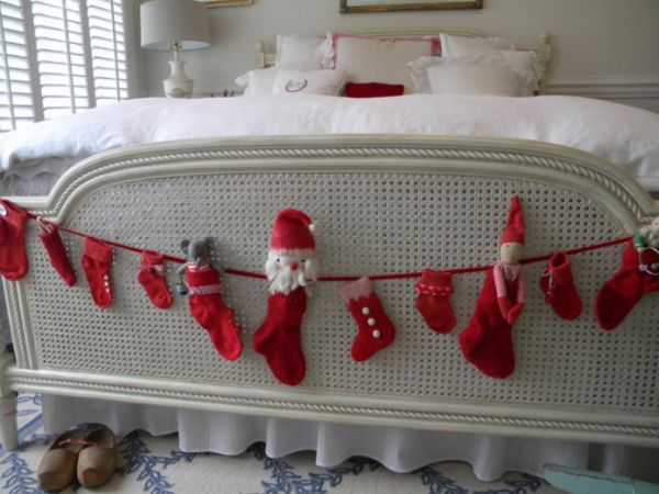 Cream and white bed and bedding, with lots of red Christmas stockings hanging over the foot of the bed