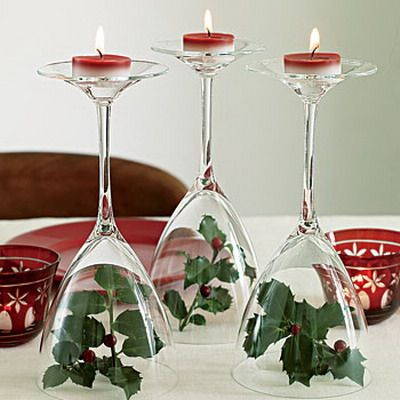 Wine glasses on a table with red tealight candles on the top