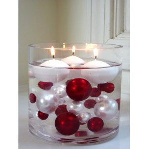 Floating candles in a white vase, which also contains red and white baubles