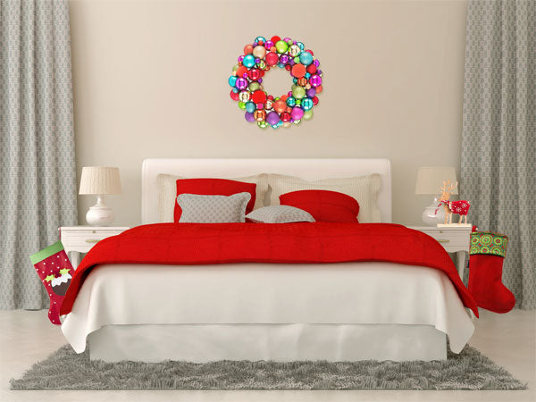 Cream bedding and bedroom with a red throw and red cushions, red Christmas stockings either side of the bed and a bauble DIY wreath above the bed