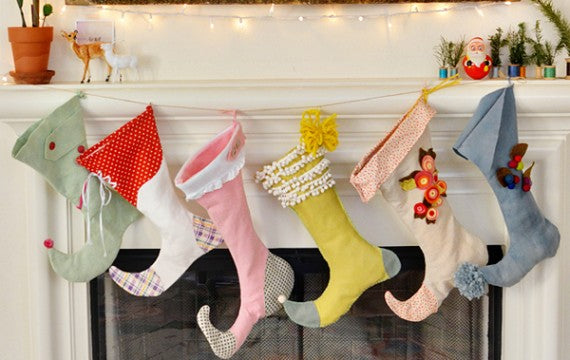 Different coloured stockings hunh at a white fireplace