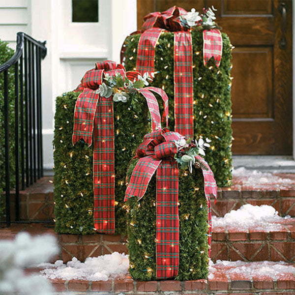 Green rectangle boxes on front door steps, wrapped in red and green checked ribbon, with fairy lights