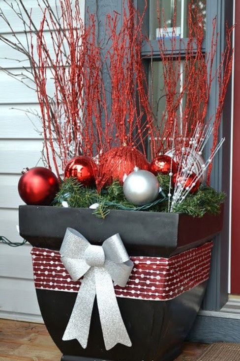 A black planter on a door step decorating with ribbon and containing red twigs, a garland and red and silver baubles
