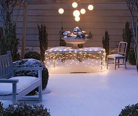 A garden covered in snow, with a table covered in fairy lights and hanging orb lights above the table