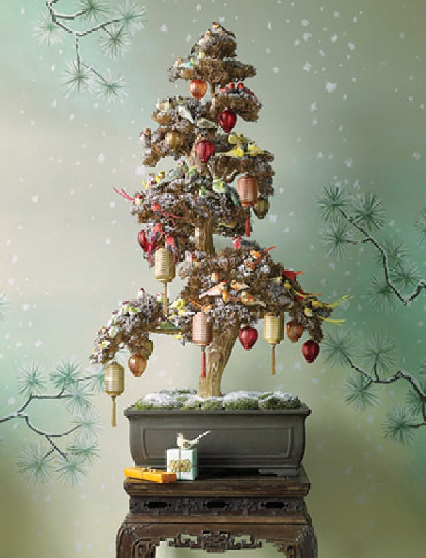 A small potted tree decorated with Christmas decorations, stood on a side table