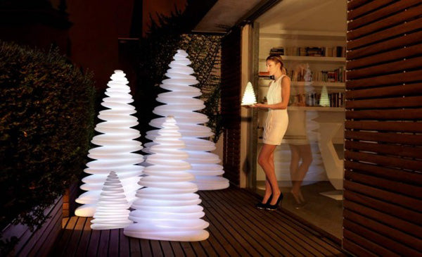 White popup Christmas tree that contain a white light, stood on decking, outside by sliding doors