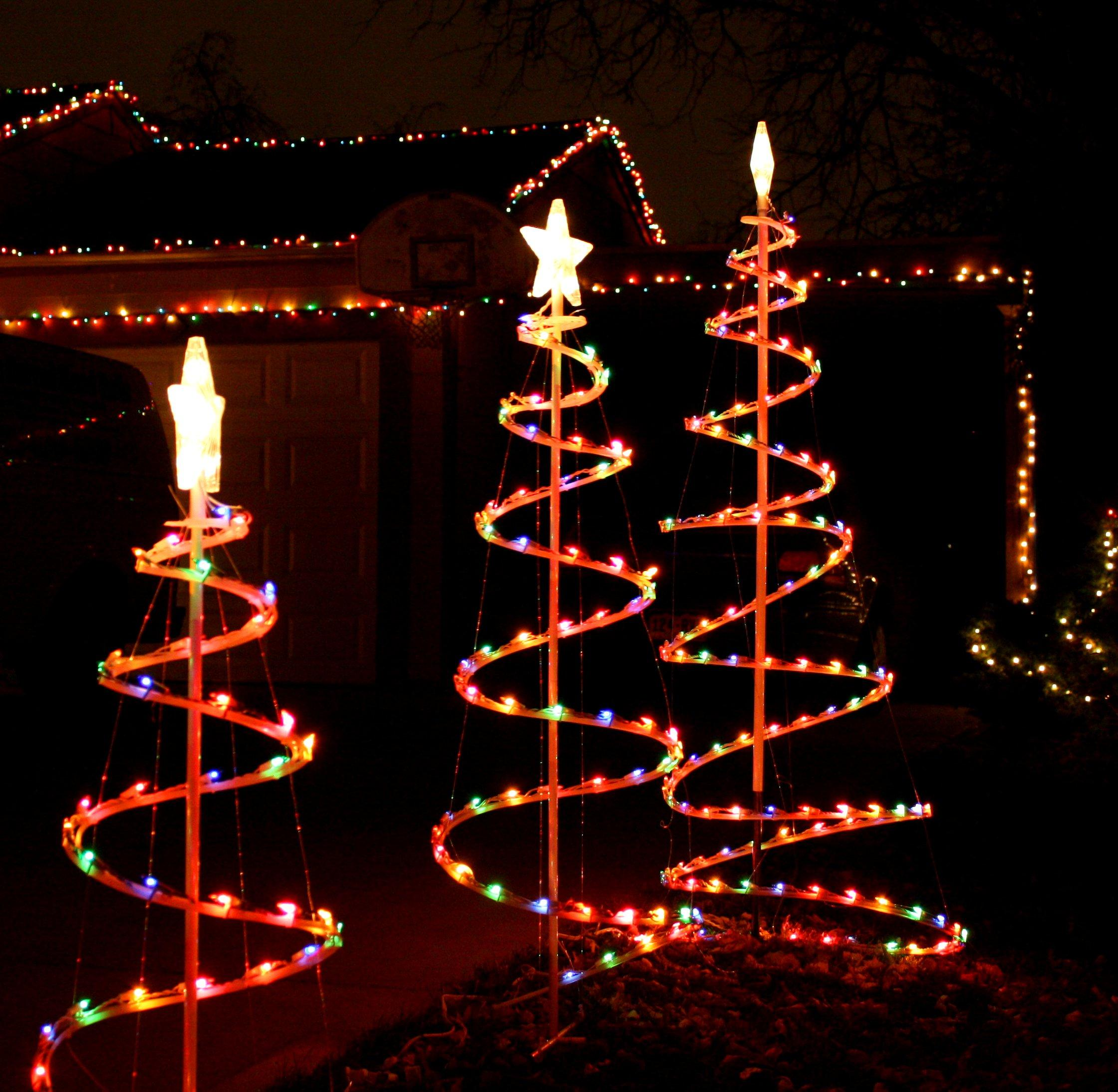Three winding spirals going around a central column, covered in Christmas lights