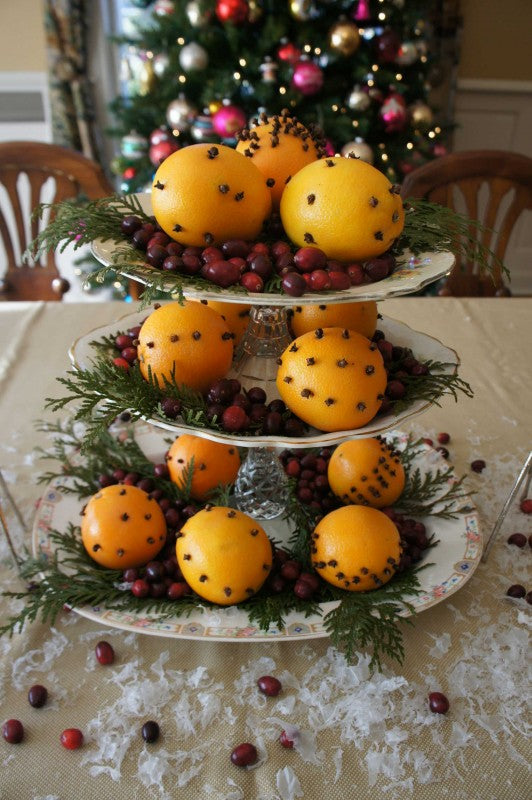 A three tier table setting with oranges and cranberries