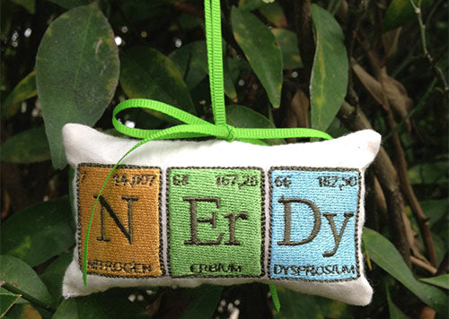 A small cushion Christmas tree decoration that shows three symbols from the periodic tables, spelling out N-ER-DY