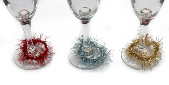 Three wine glasses on a table with red, blue and gold glitter wrapped around each one