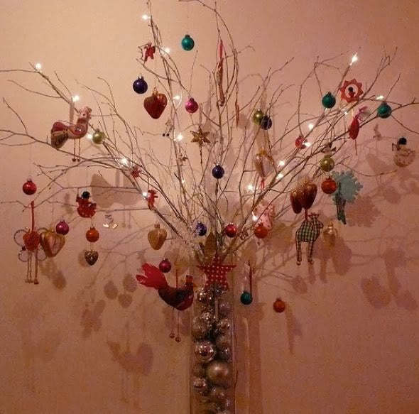 Glass cylinder vase containing twigs decorating with Christmas baubles