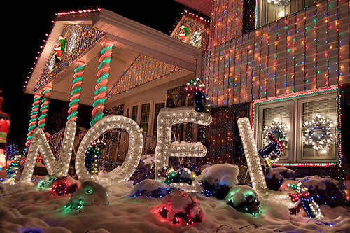 NOEL letters outside a house, with Christmas lights all over the house