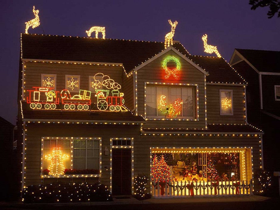 A house with outside Chrismtas lights depicting the Polar Express and reindeer on the roof