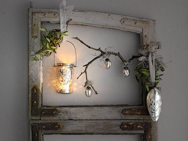 Old cabinet door with glass removed, decorated with branch, tree ornaments and candle holder