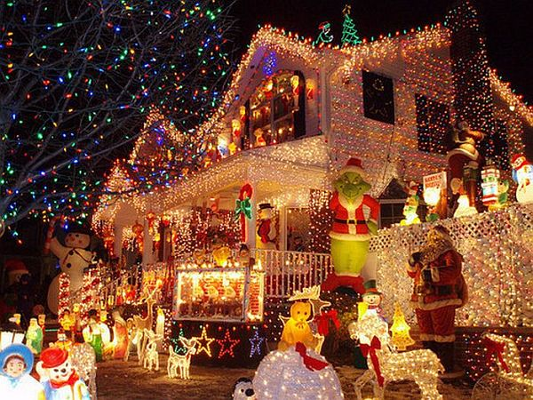 A large house covered in Christmas lights with snowmen, Santa and a large Grinch