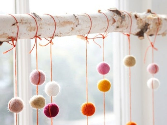 A white tree branch with string and coloured pompoms hangings off it