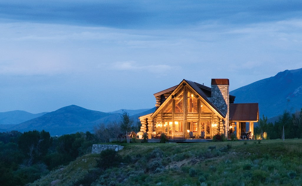 A log cabin illuminated by beautiful outdoor lights at dusk