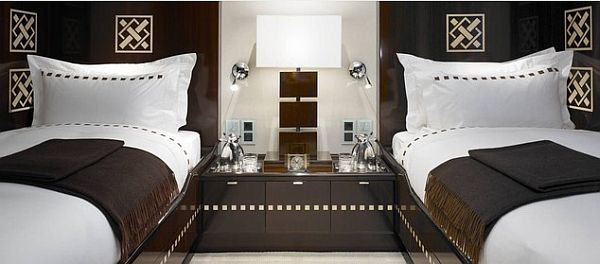 Two single beds on either side of the room, with white and dark brown bedding and decor