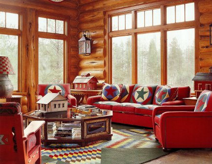 Log cabin with large bright windows and red sofa and arm chairs