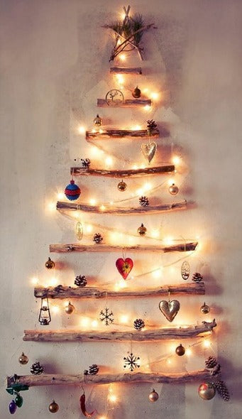 Different sized branches stacked and spaced on out a wall to look like a Christmas tree, decorated with ornaments and Christmas lights