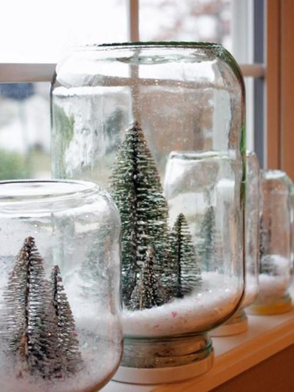 Upside down glass jars turned into snow globes, containing little Christmas trees
