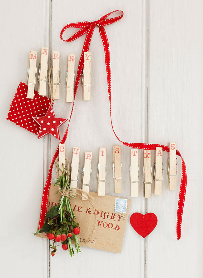 Wooden clothes pegs and red ribbons create a festive decoration