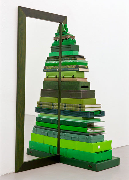 Half of a Christmas tree made from lots of green boxes, stood next to a mirror to create a full tree