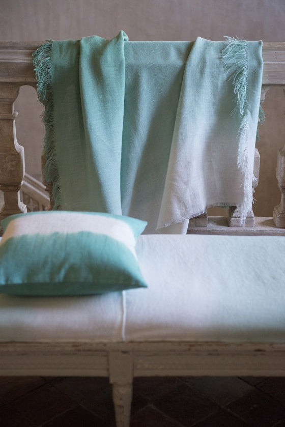 White and light green throw and matching cushion, draped over a white bench