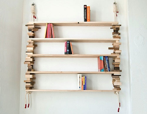 A wooden rope shelf hung on a white wall