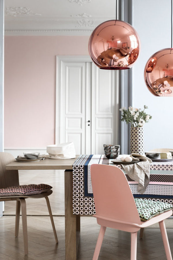 A dining room with pink chairs, pink wall in the background and rose gold (copper) light fixtures