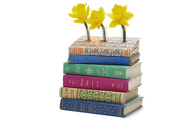 A pile of books with flowers growing through them