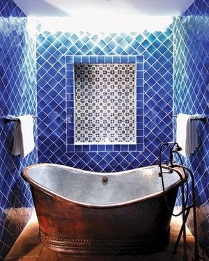 Small bathroom with diamond shaped blue tiles and an old fashion copper bathtub