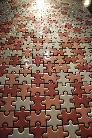 Flooring made from red, bronze and grey coloured jigsaw pieces