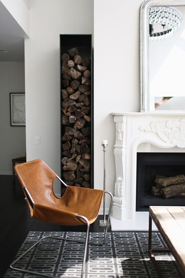 Black and white living room, with brown leather chair, next to a white fireplace