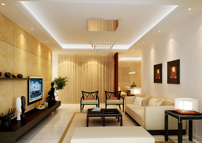 A white and cream living room with white sofa pointing at a wall mounted TV, on a cream tiled wall