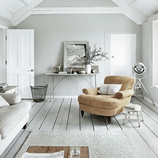 White and light grey living room with beige armchair and cream sofa