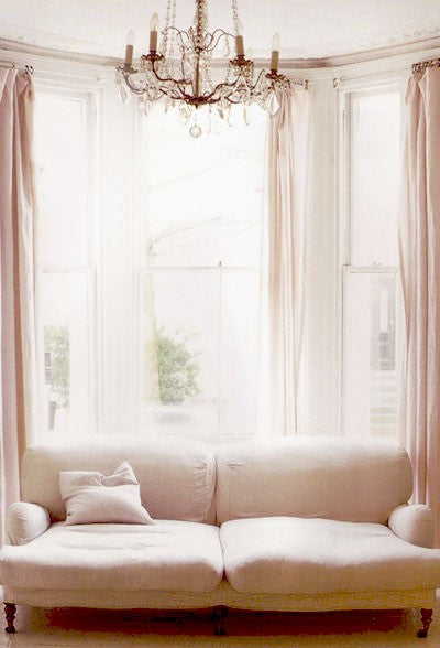 Large bay window with white voile panels and pink blush pencil pleat curtains