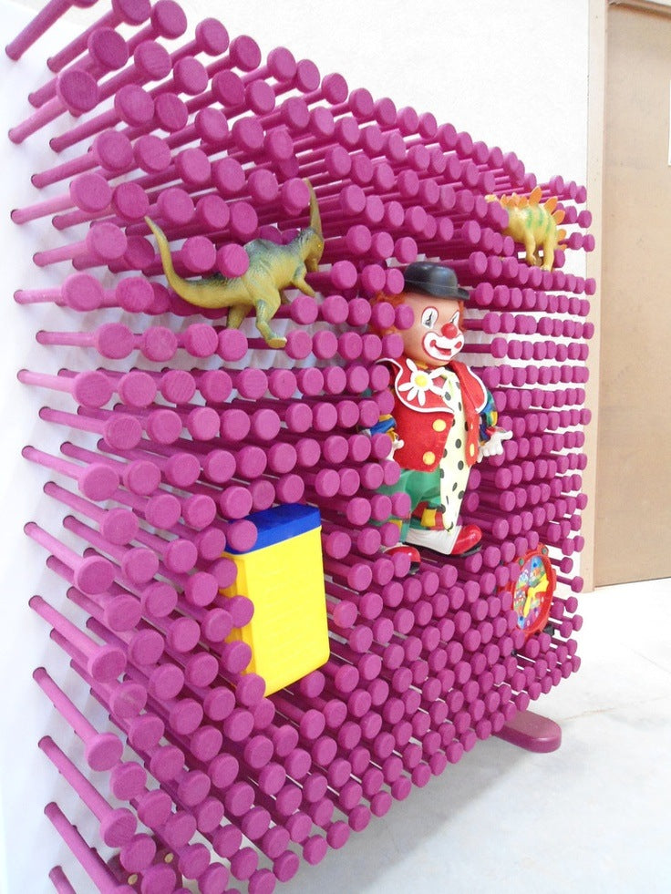 Large pinart wall in pink, where toys can be pushed into the wall and held in place