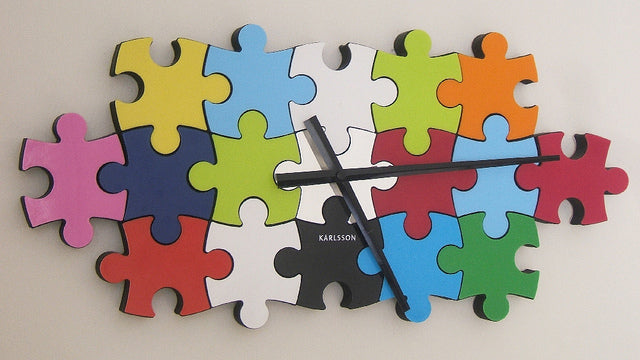 Wall clock with face made from coloured jigsaw pieces