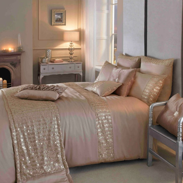 Blush pink silky bedding, with lamps and candles in the background