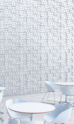 A canteen dining area with a wall covered in white jigsaw pieces