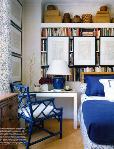 Blue and white bedding, with blue wooden chair next to a white desk