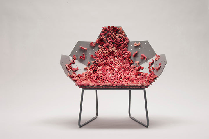 A funky geometric grey metal chair, seemingly covered in pink rose petals