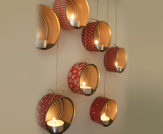 Biscuit Tins Hanging Against A Wall Being Used To Hold Lit Candles