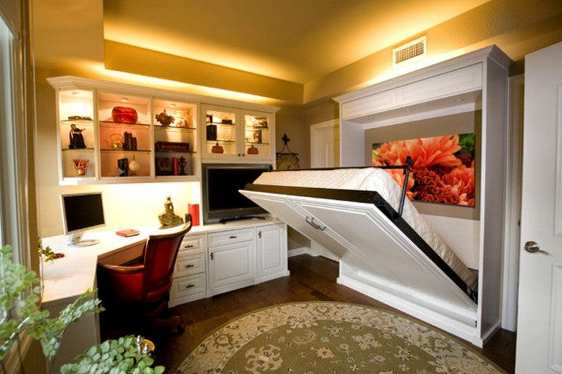 A home office with fold out bed, that folds down from a white wardrobe