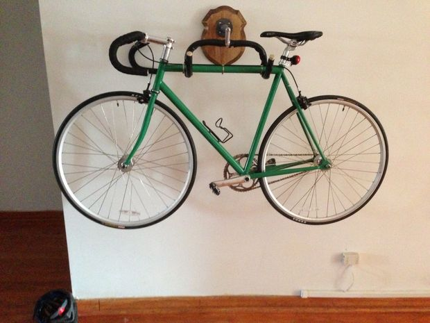 A bicycle hung on the wall, using wall mounted handlebars