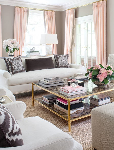 A beige and pink salmon living room with classy white sofas, armchairs and brown patterned cushions