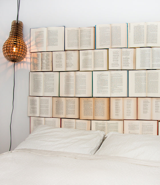 A headboard for a bed made from open books