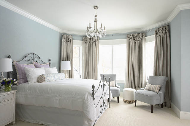 Light blue bedroom with metal frame bed, with white bedding and bay window in the background with beige curtains